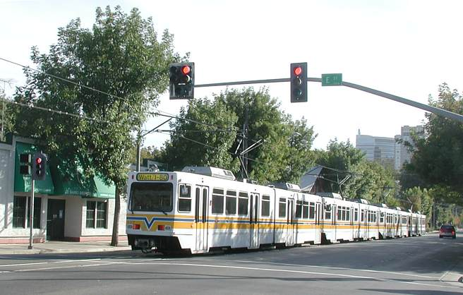 An impressively long light rail train rides along its reserved portion of street pavement on 12th St. The train is stopped for a red signal at E St. on this ... & Waiting for Street Traffic